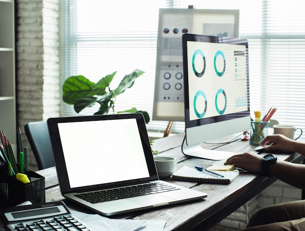 オフィスのヒップスターのテーブルの上に空白の画面を持つノートパソコン