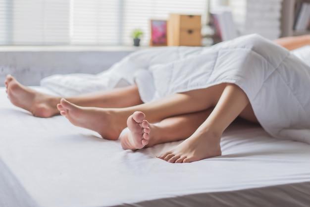 ベッドの上でセックスをしている情熱的な若いアジアカップルのクローズアップ。彼らはセックスにうんざりしています。