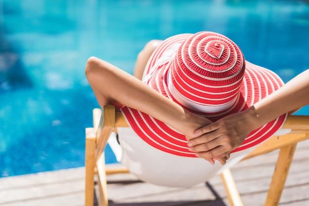 女性は夏にリラックスできる椅子に座っています。