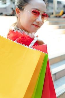 女性の幸せな笑顔サングラスをかけて買い物袋でポーズをとると市内のカメラ目線