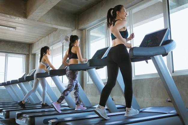 運動のためのトレッドミルの概念にジムで走っている女性