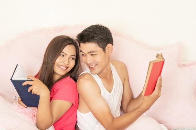 カップルは一緒に本を読んで、恋人はベッドで幸せです