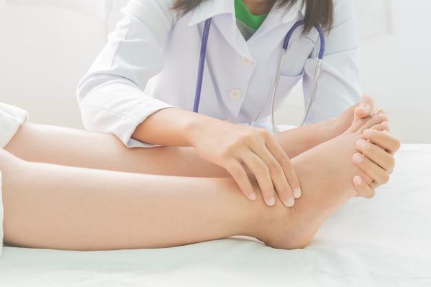 妊娠中の女性とベッドの上の医者の足の腫れ