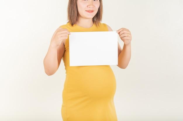 妊娠中の女性そして小さな紙のラベル。