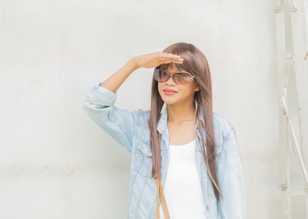 Молодая девушка в темных очках и солнечном свете с естественным освещением