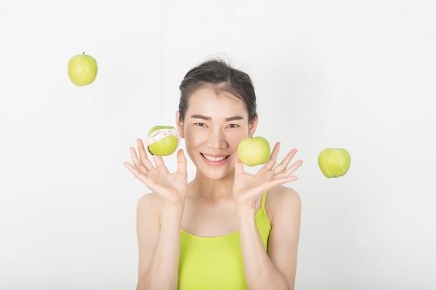 Здоровые женщины с зелеными яблоками в белой сцене