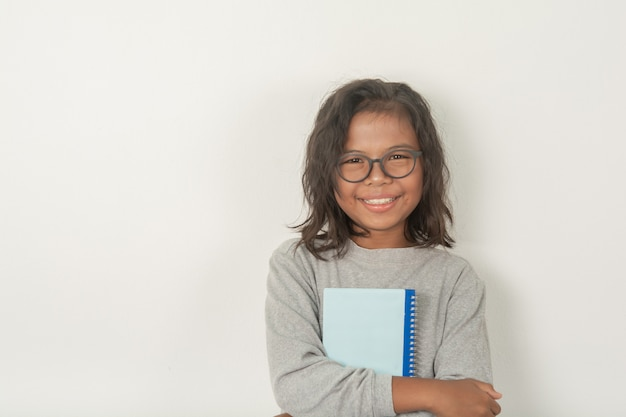 女の子は眼鏡をかけ、顔の写真を撮り、カメラを見ます。抱擁で明るくて魅力的な本があります。灰色のシーン