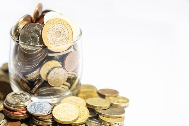 貨幣の瓶、様々な通貨のコインは、白い背景にあふれている