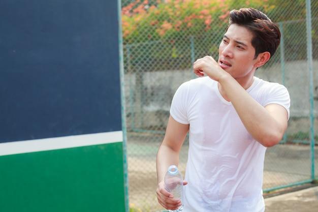Измученный потный спортивный мужчина, держащий чистую свежую бутылку минеральной питьевой воды