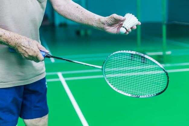 男性シニアバドミントンシングルプレーヤーの手は白いシャトルコックを保持します