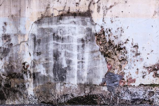 普通の古い高齢者の白い着色された塗装ひびの入ったセメントコンクリート家の壁の表面の背景に風化テクスチャパターン。