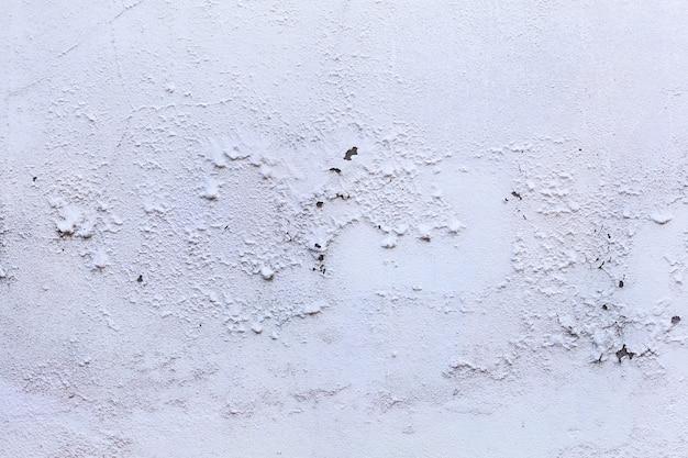 普通の古い高齢者の白い着色された塗られた塗られたコンクリートの家の壁の表面の背景に風化した皮をむいたテクスチャパターンを色あせた。