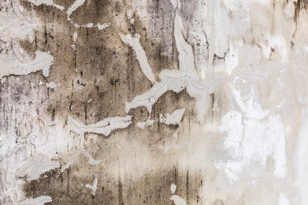 ひびの入ったセメントコンクリート壁表面の背景に古い高齢者白塗装色褪せ風化テクスチャ