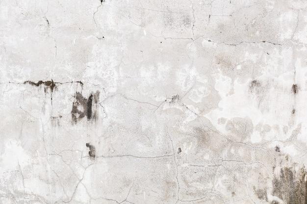 ひびの入ったセメントコンクリート壁の表面の背景に古い高齢者の白い色塗装色あせたテクスチャパターン