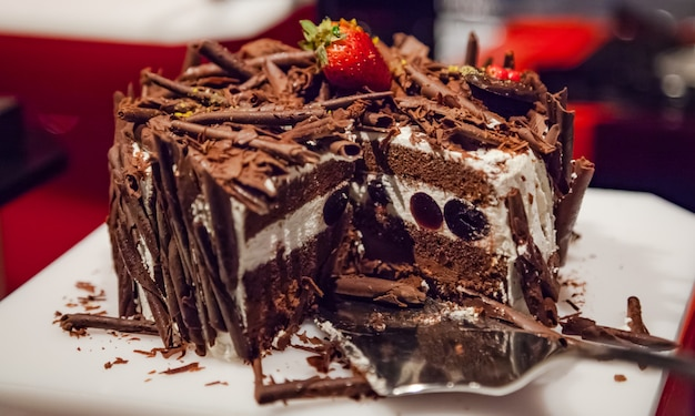 Вкусный многослойный шоколадный торт, украшенный тертым шоколадом и клубникой