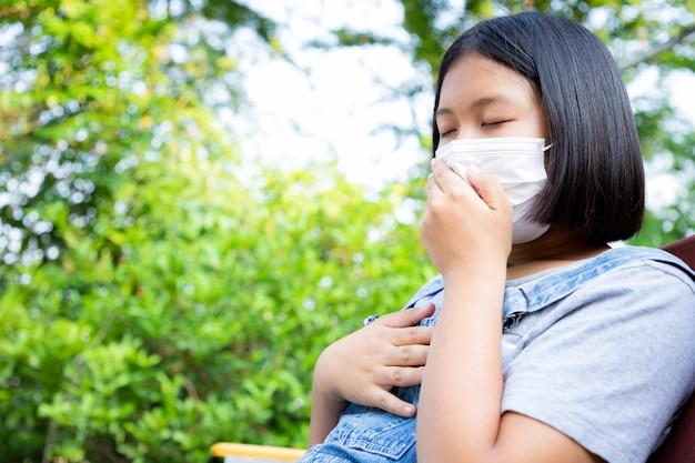 Молодая девушка носит защитную маску и имеет головную боль и карантин, чтобы следить за инфекцией от вируса в саду дома. понятие социальной дистанции.