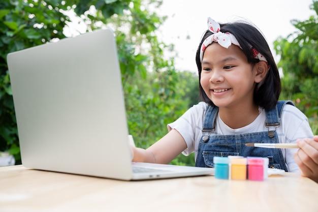 Две маленькие девочки учатся через онлайн-уроки в палисаднике.