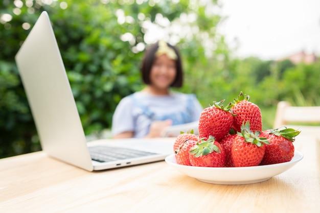Группа клубники размещается на белой тарелке перед ноутбуком в саду перед домом на фоне молодой девушки, работающей или выполняющей домашнюю работу, отправляющей учителя.