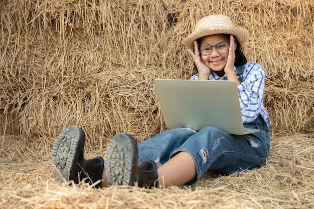 若い女の子は眼鏡をかけ、ノートブックを使用して、納屋の干し草でリラックスしながら農業を勉強します。自由。