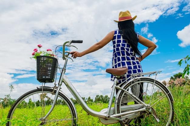 後ろから、女性は茶色の帽子を着用し、自転車のビンテージの近くに立つ美しいフロ