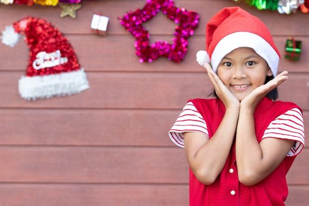 赤いドレスの若い女の子は、クリスマスに挨拶を受けた後、手から心臓の形を示します