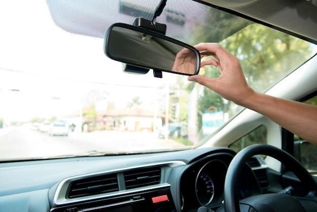 ドライバーの手は車のリアビューミラーを調節して視界を良くし、車を止める