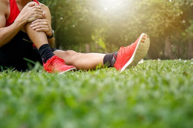 Атлетический мужчина с болью в ногах и коленях. спорт, осуществляющий травму. концепция здравоохранения.
