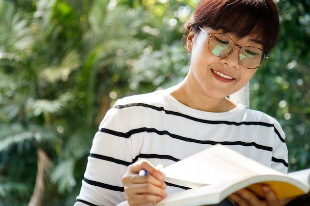 Азиатская студентка делает домашнее задание с усердием, сидя в университете.