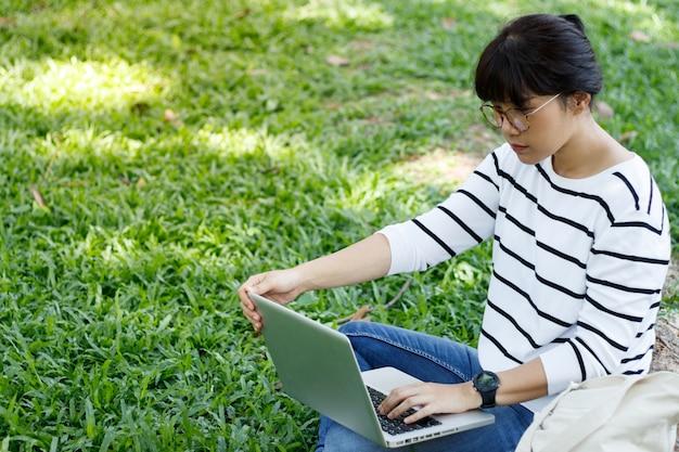Азиатская студентка делает домашнее задание в замешательстве, сидя в университетском городке.