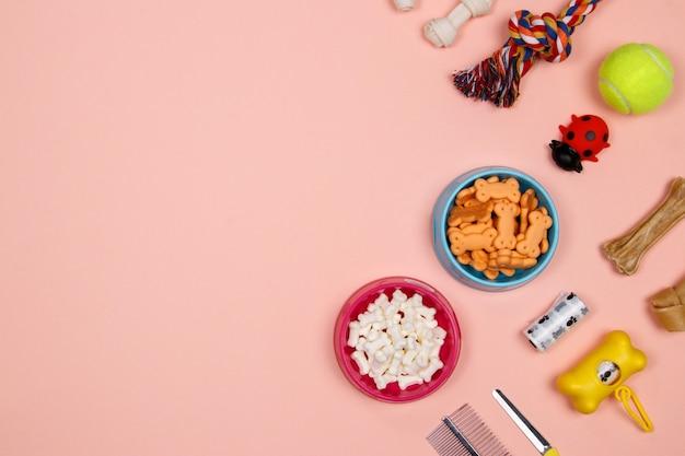 Аксессуары для собак, продукты питания и игрушки на розовом фоне.