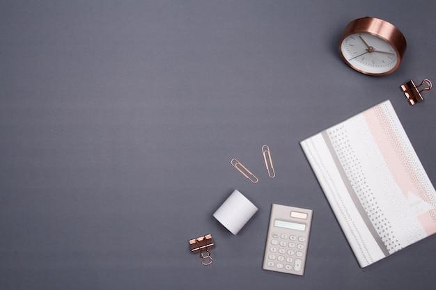 Офисный стол со смартфоном и другими канцелярскими принадлежностями на сером фоне.