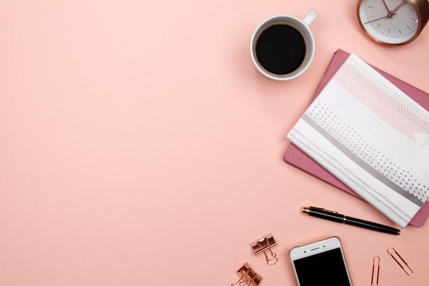 Офисный стол со смартфоном и другими канцелярскими принадлежностями на розовом фоне.