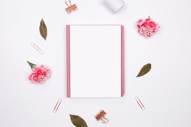 Макет дневник с розовым гвоздики цветок на белом фоне.