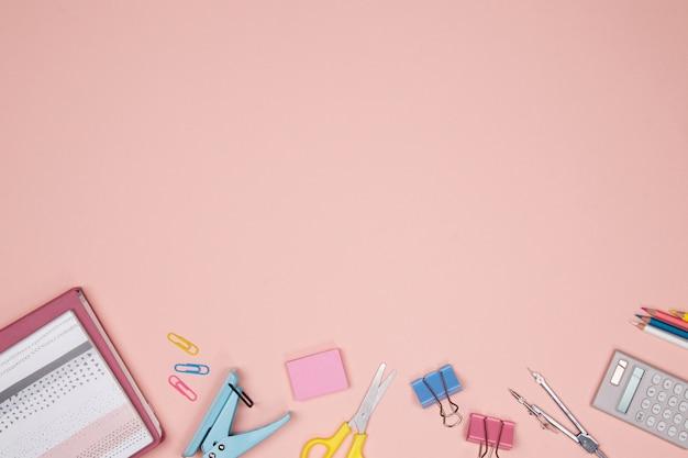ピンクの背景にステーショナリーと事務用品。フラットレイ。学校のコンセプトに戻ります。