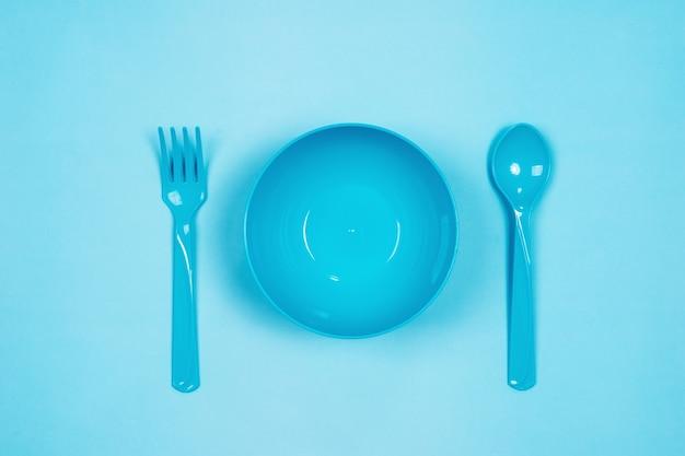 Набор пустой голубой пластиковой посуды миски, ложки и вилки