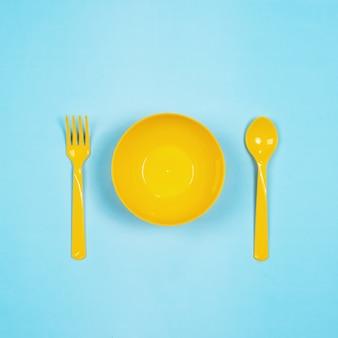 Набор пустых желтых пастельных пластиковых посуды миски, ложки и вилки