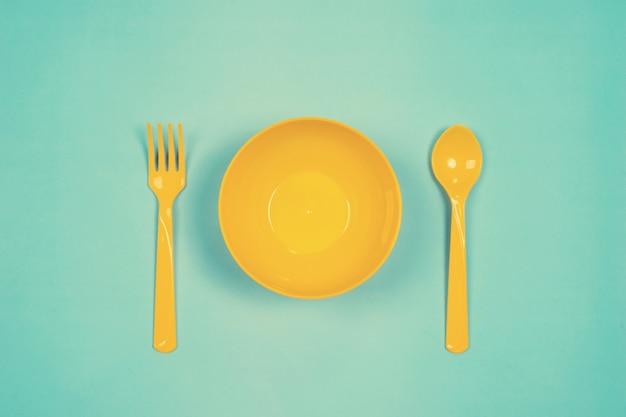 Набор пустой желтой пластиковой посуды миски, ложки и вилки