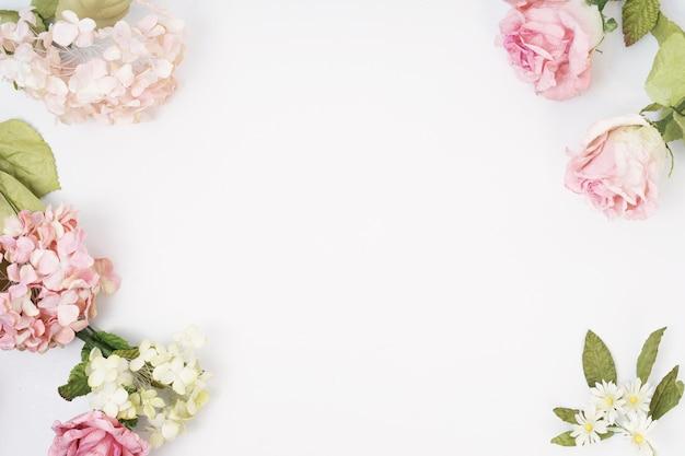 ピンクとベージュのバラ、白い背景に緑の葉で作られたフレーム。