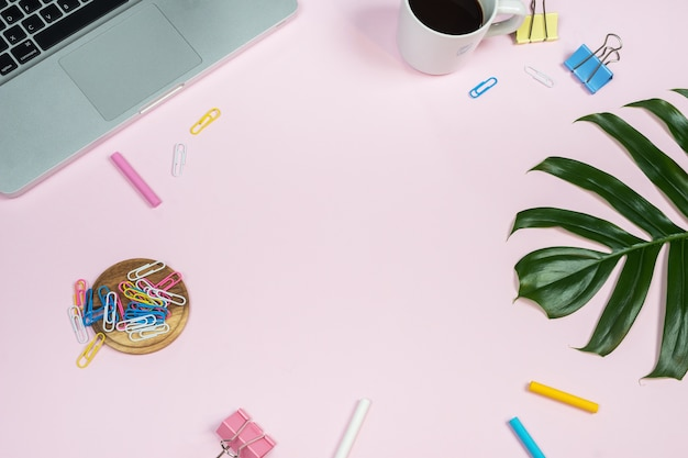 Рабочее место для рабочего стола с ноутбуком и аксессуарами на розовом фоне.