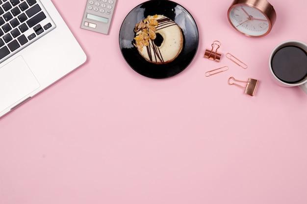 Плоский лежал рабочий стол рабочего стола рабочего пространства на розовом фоне. вид сверху.