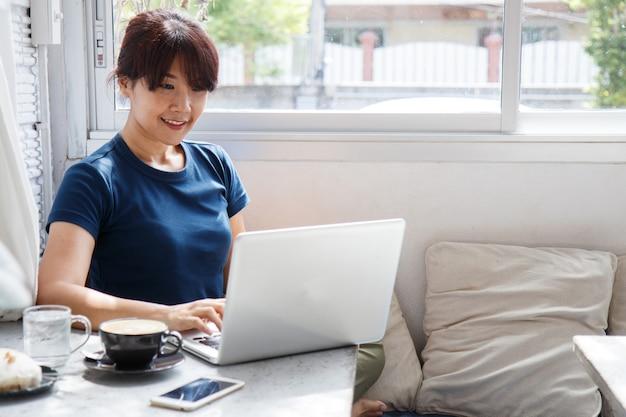 Улыбается женщина, смотреть видео на портативный компьютер в уютной совместной рабочий интерьер,