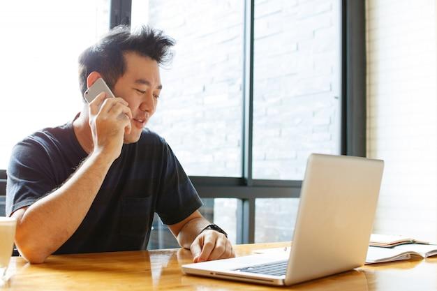 Веселый азиатский мужчина малого бизнеса, разговаривающий по телефону с клиентом
