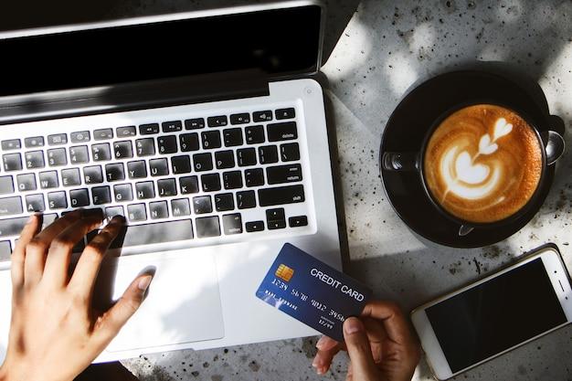 Закройте вверх по руке женщины держа кредитную карточку и оплачивая на компьтер-книжке