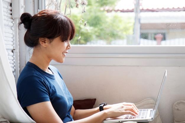 Молодая азиатская женщина используя тетрадь портативного компьютера на кофейне. концепция электронного обучения - изображение.