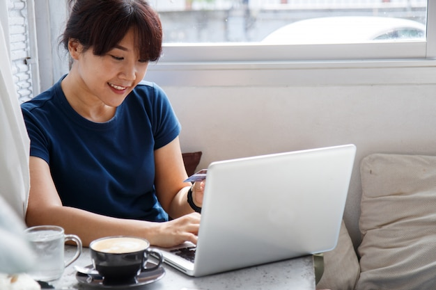 アジアの若い女性がクレジットカードのモックアップを押しながらカフェに座っている間ラップトップコンピューターを使用して。
