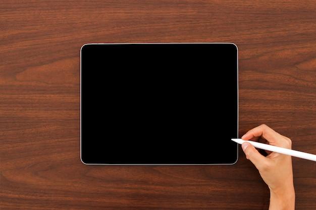 木製の背景に手でデジタル鉛筆でデジタルタブレットデバイスのモックアップ。