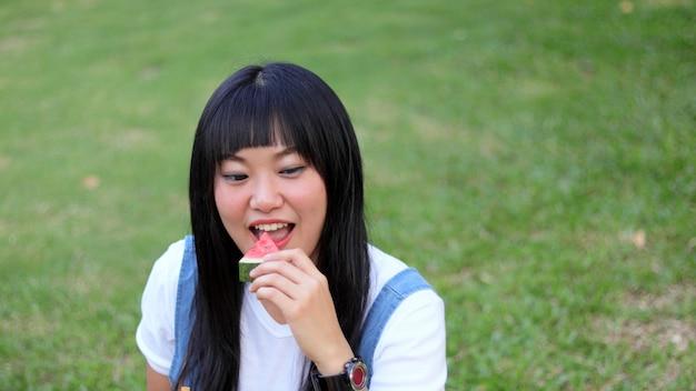 Азиатская молодая красивая женщина ест свежий арбуз с улыбкой счастливым на открытом воздухе на прекрасный день.