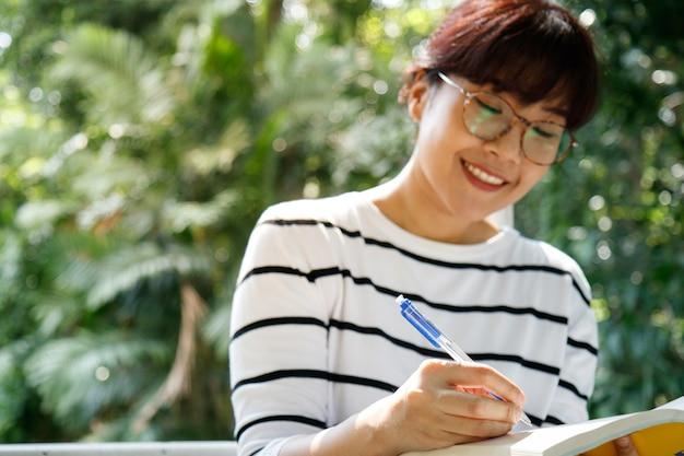 Азиатская студентка делает домашнее задание, сидя в университете.