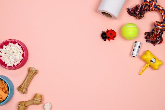 Аксессуары для собак, продукты питания и игрушки на розовом фоне. квартира лежала. вид сверху.