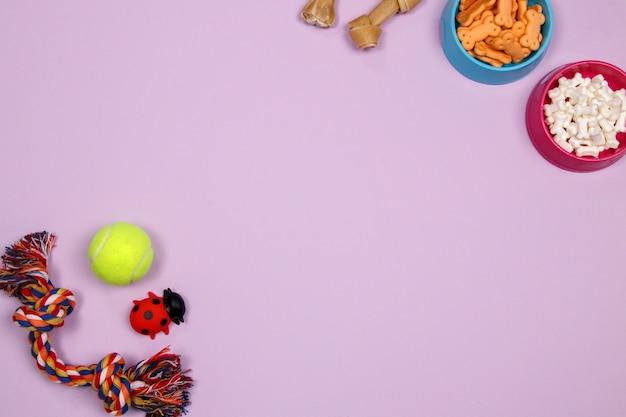 犬のアクセサリー、食品、おもちゃ、紫色の背景。フラットレイ。上面図。